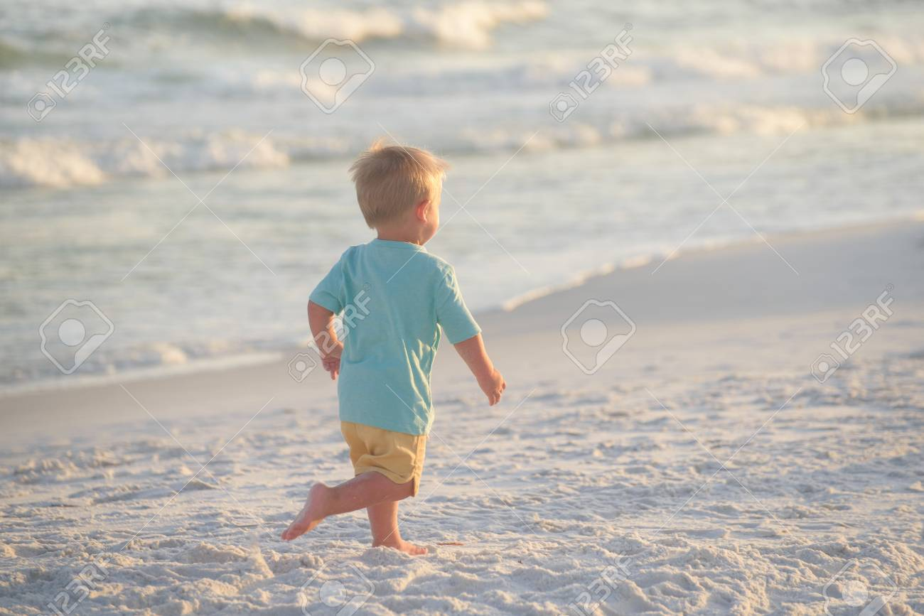 bfe0b2b10 Little boy in blue shirt and yellow shorts running on sand on the beach,  towards
