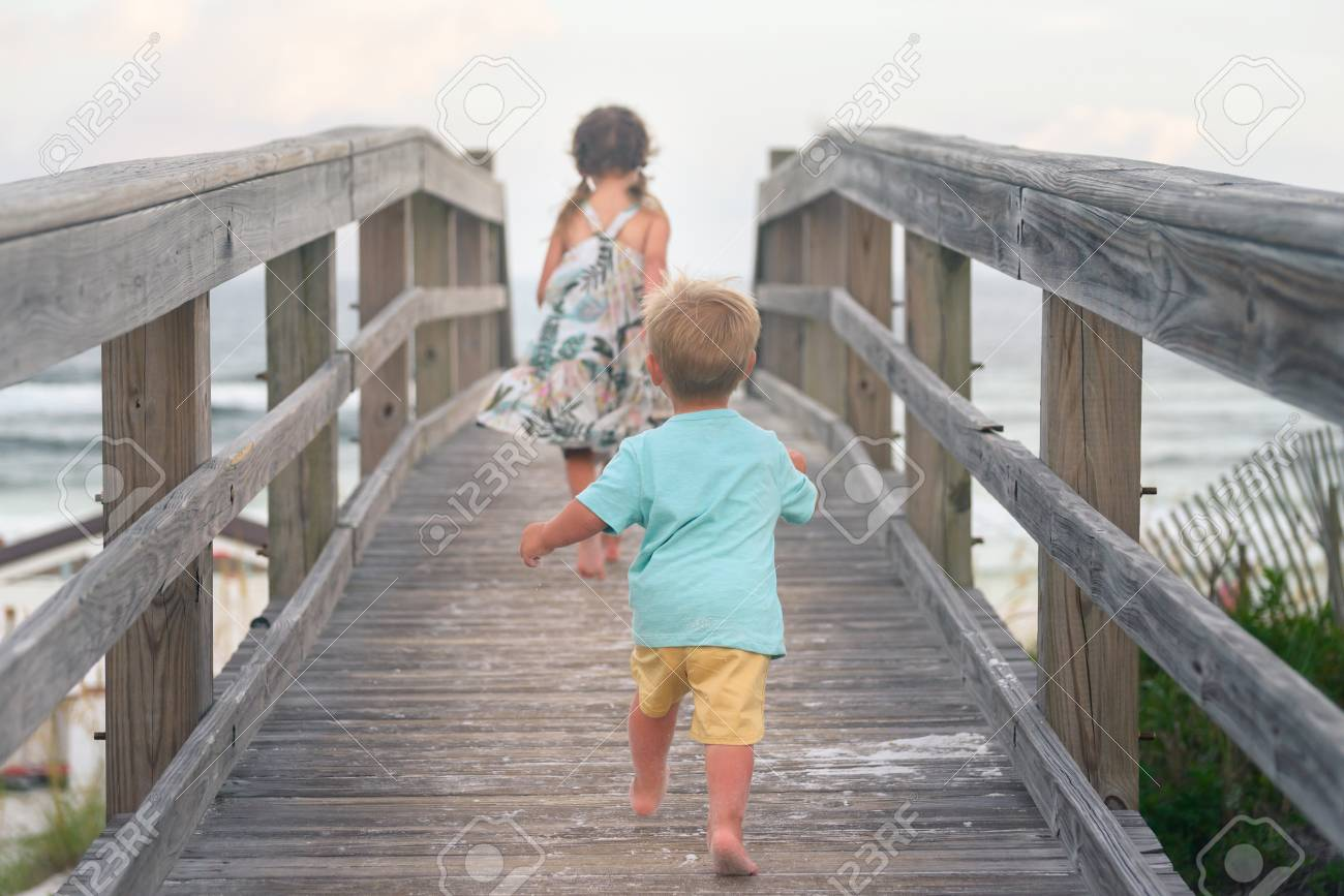 Niño Y Niña Corriendo En La Terraza De Madera En La Playa