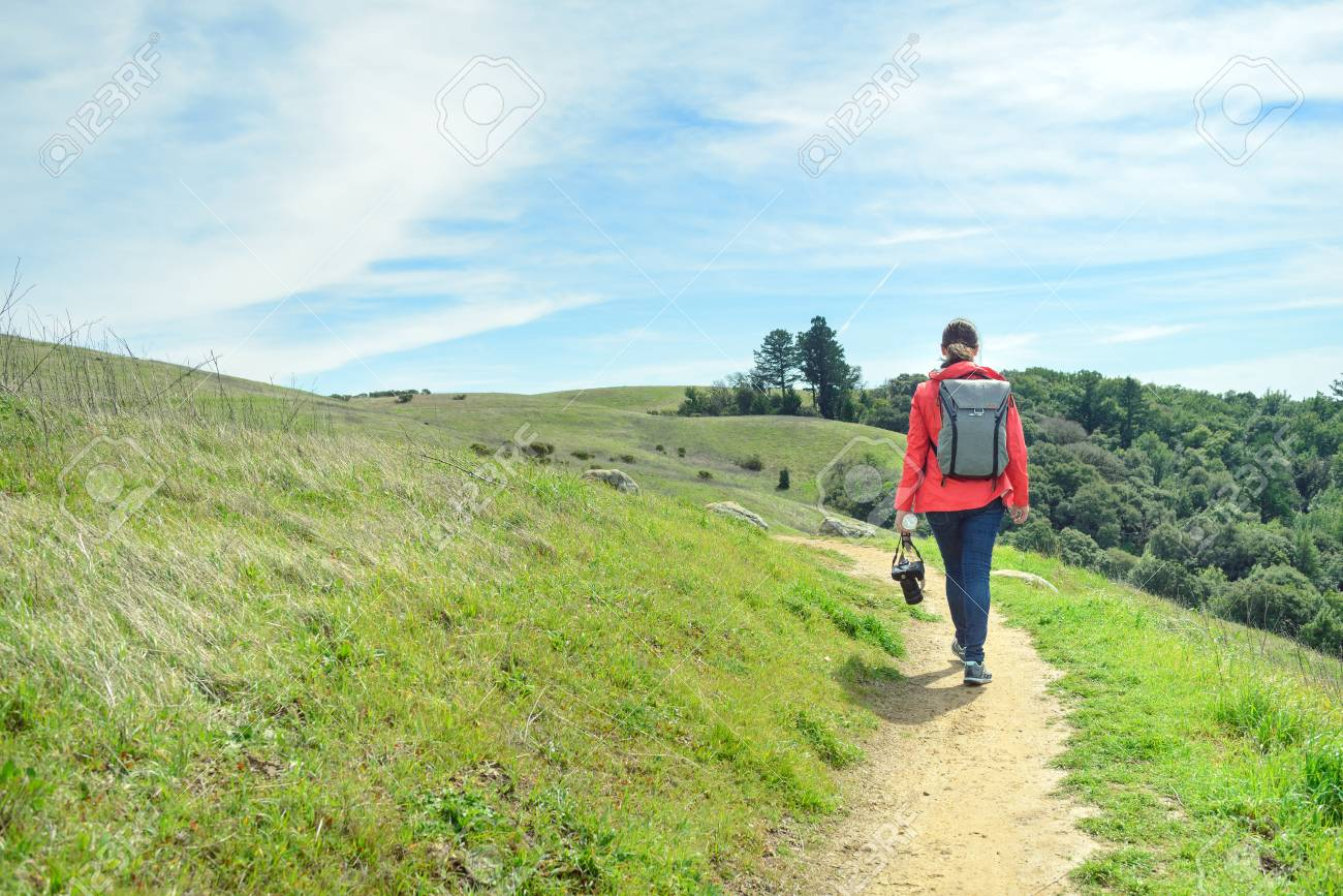 Hiker in red jacket with backpack on trail in beautiful landscape - 104878715