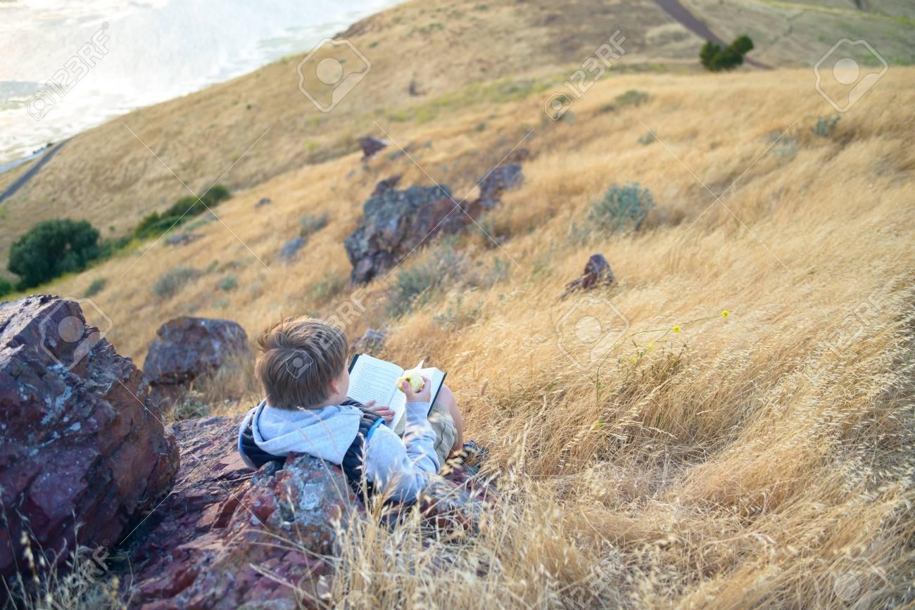 Boy reading book outside - 105112960