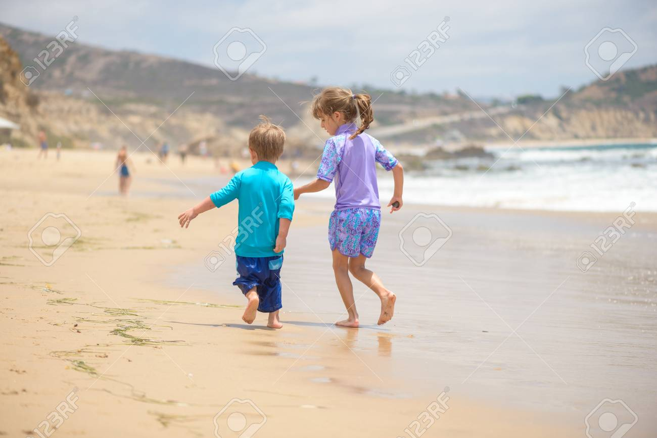Happy kids running on the beach near the ocean - 106235230