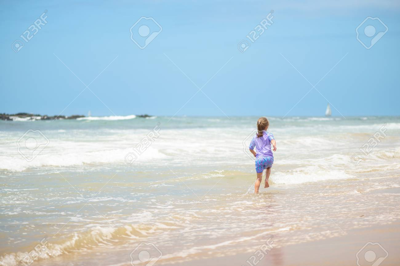 Happy girl running on the beach in the waves - 106235231
