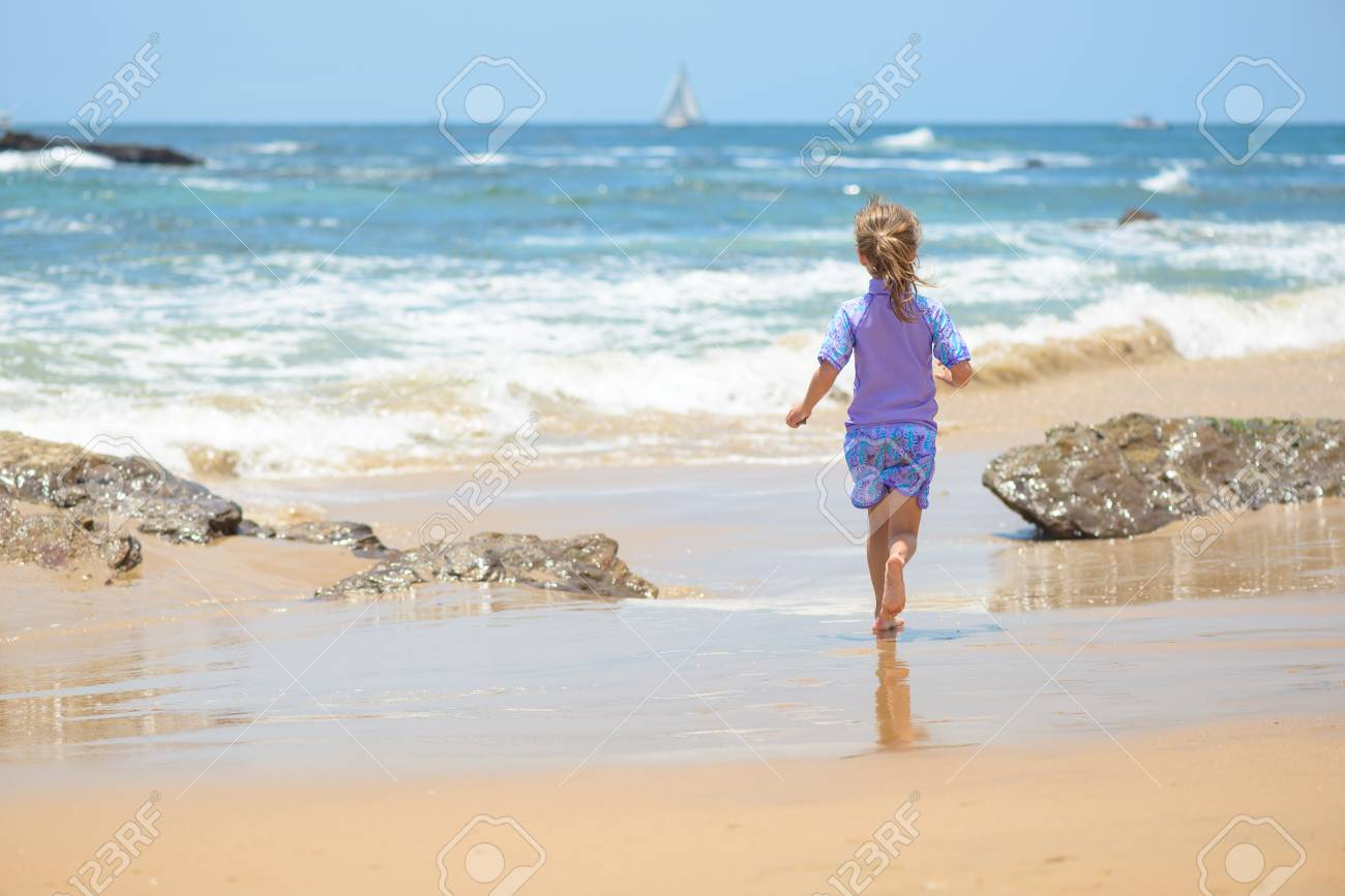Happy girl running on the beach to the ocean - 106235232