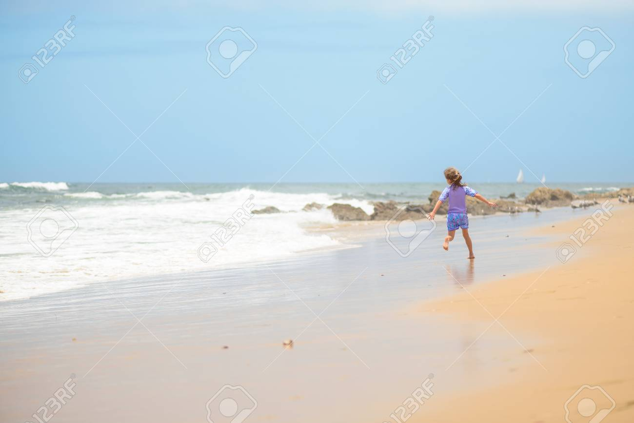 Happy girl running on the beach in the waves - 106235233