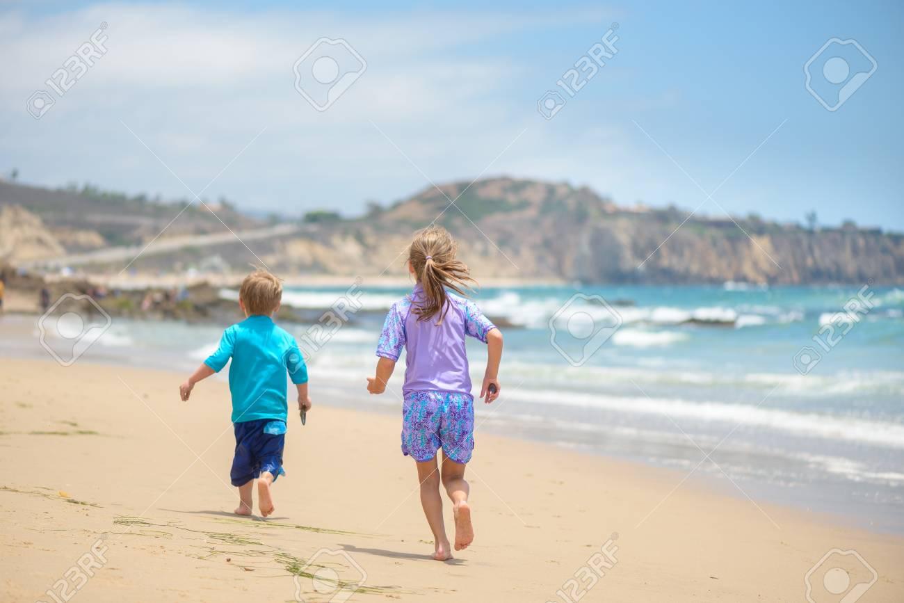 Happy kids running on the beach near the ocean - 106235234
