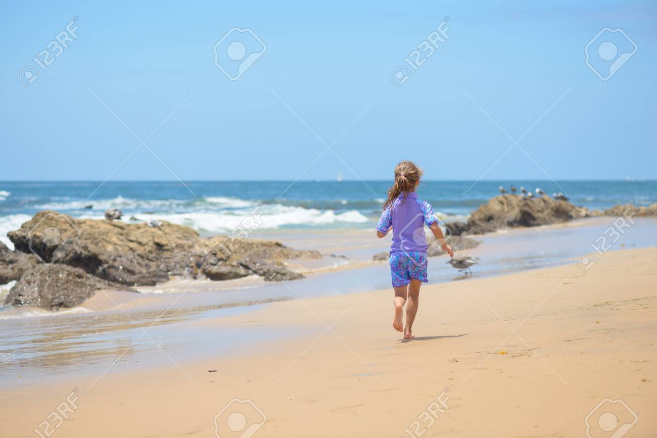 Happy girl running on the beach to the ocean - 106235235