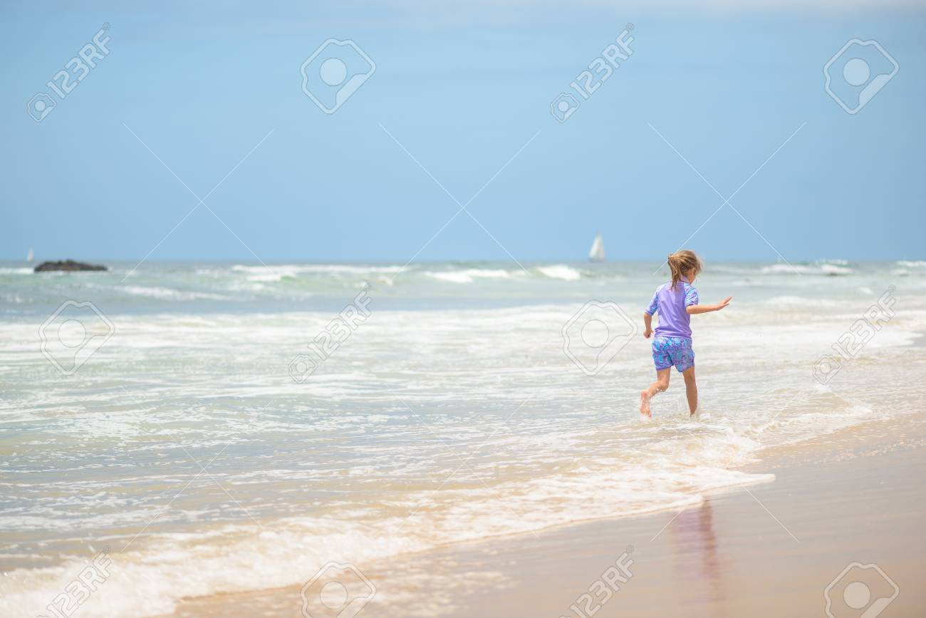 Happy girl running on the beach in the waves - 106235237