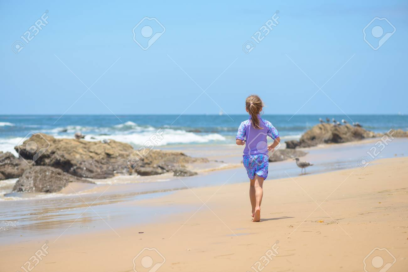 Happy girl running on the beach to the ocean - 106235239