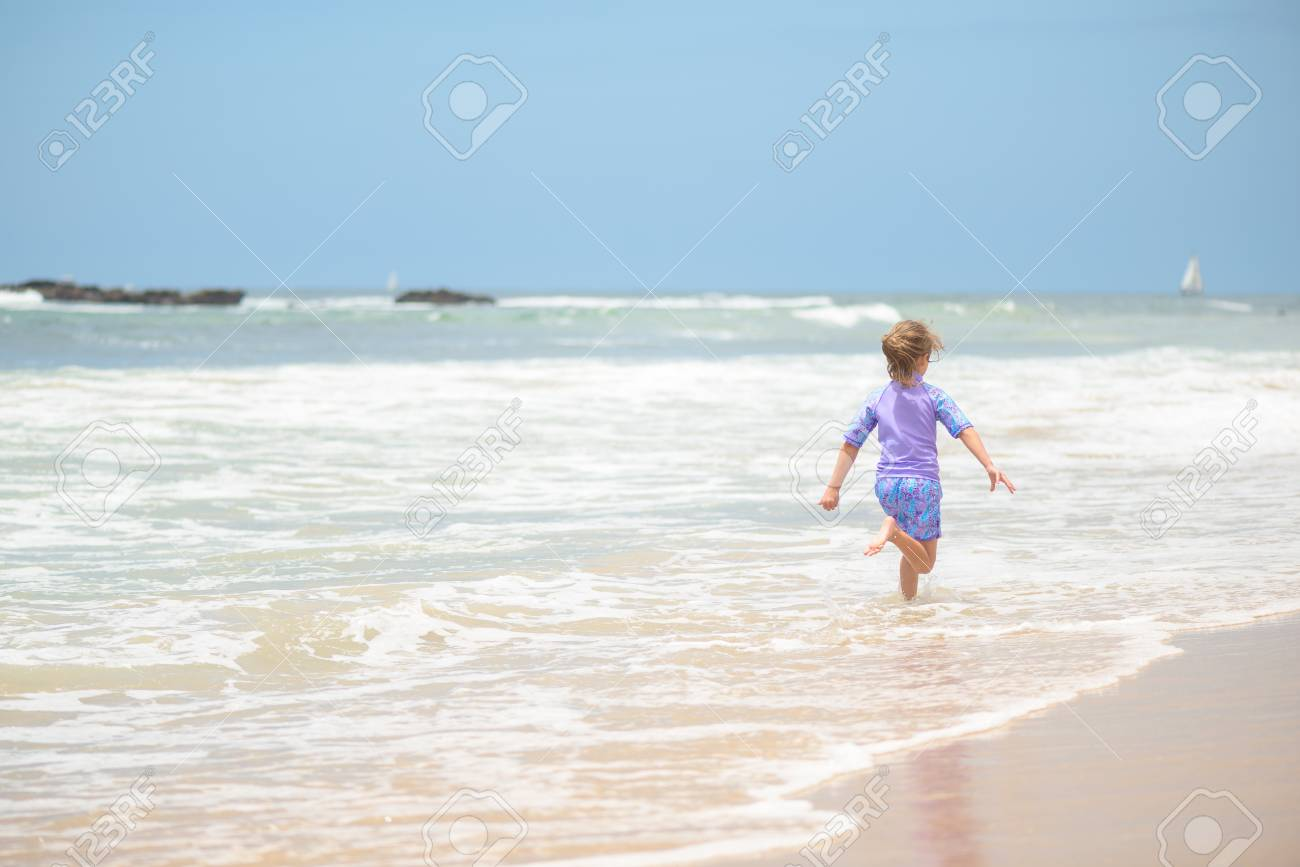 Happy girl running on the beach in the waves - 106235241