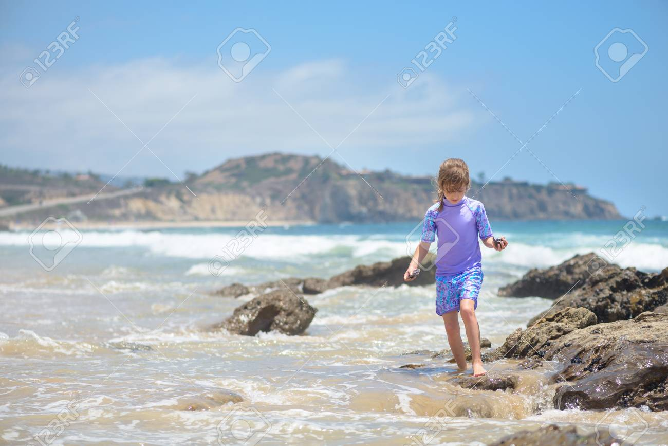 Happy girl playing on the beach in the rocks - 106235242