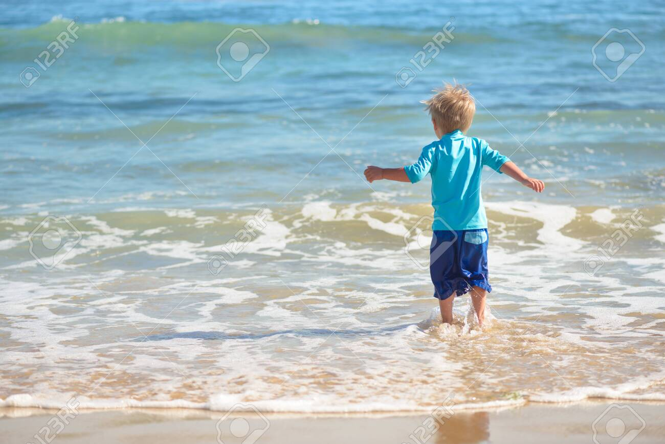 Happy boy running on the beach in the waves - 115343668