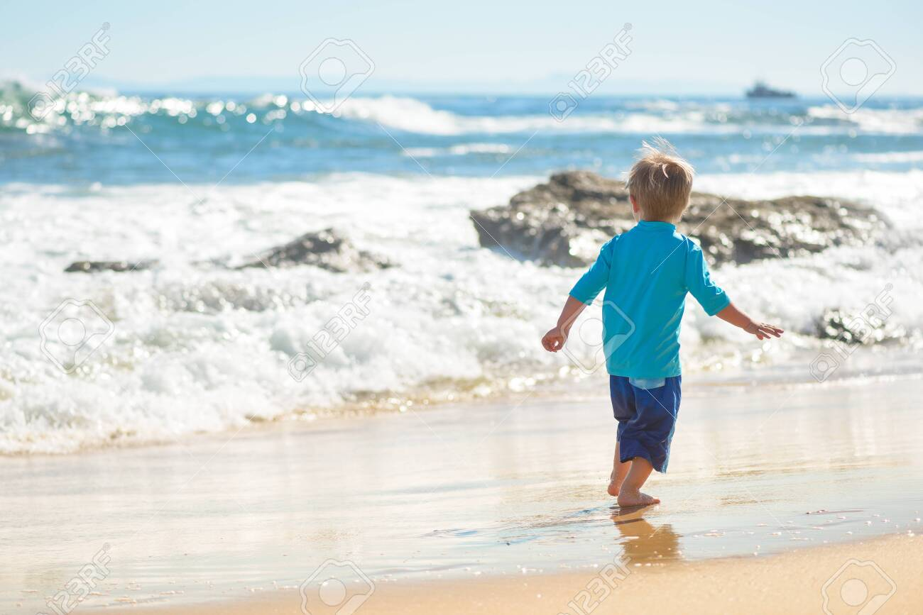 Happy boy running on the beach in the waves - 115343690
