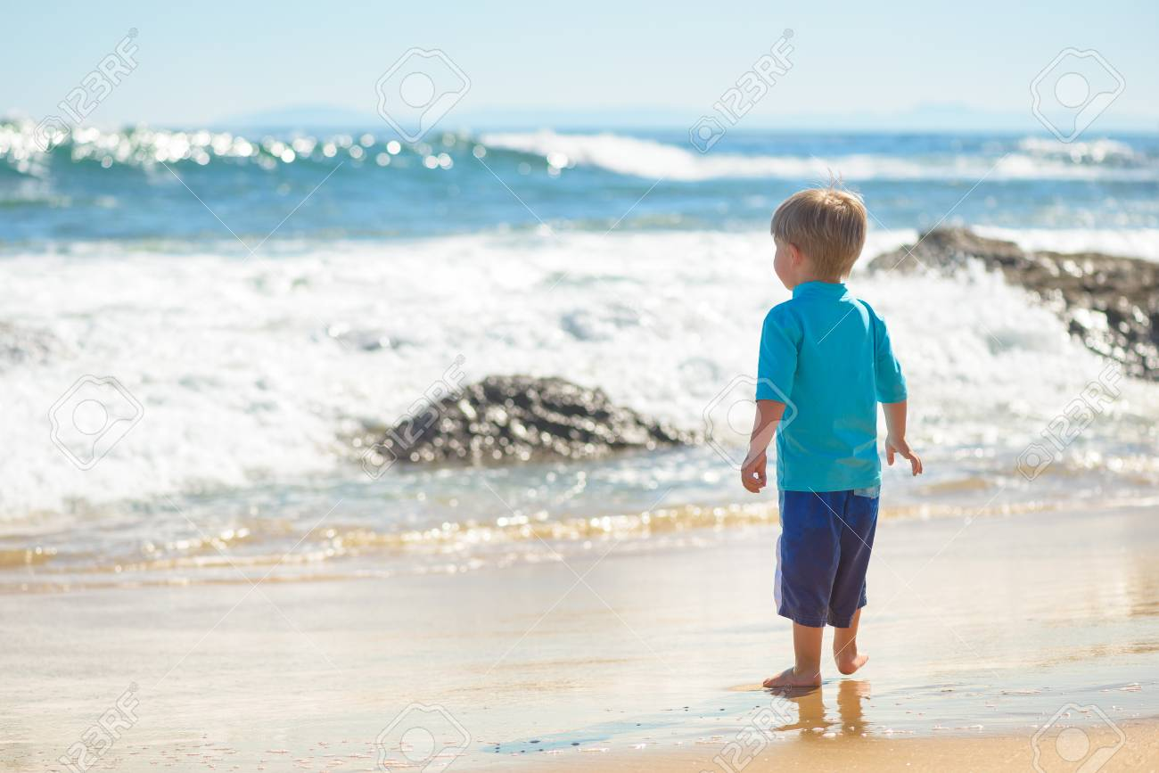 Happy boy in blue swimsuit running on the beach in the waves, family on vacation, view from behind - 115343692