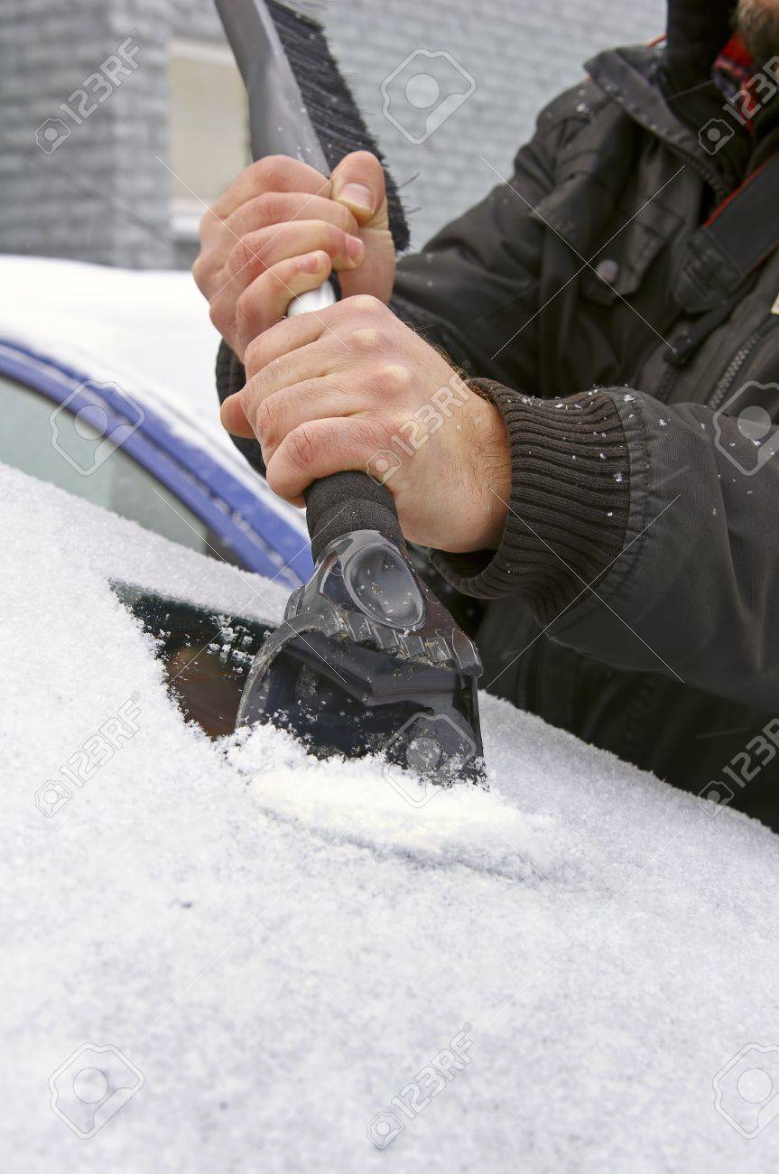 scraping snow and ice from the car windscreen Stock Photo - 8494704