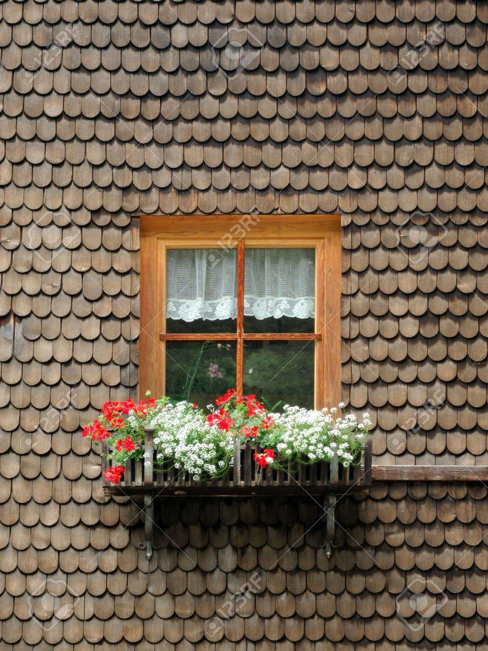 Vintage wooden window frame with curtain and flowerpot stock - Ancient Wooden Window With Flowers Surrounded By Timber Shingles Stock Photo 14774344
