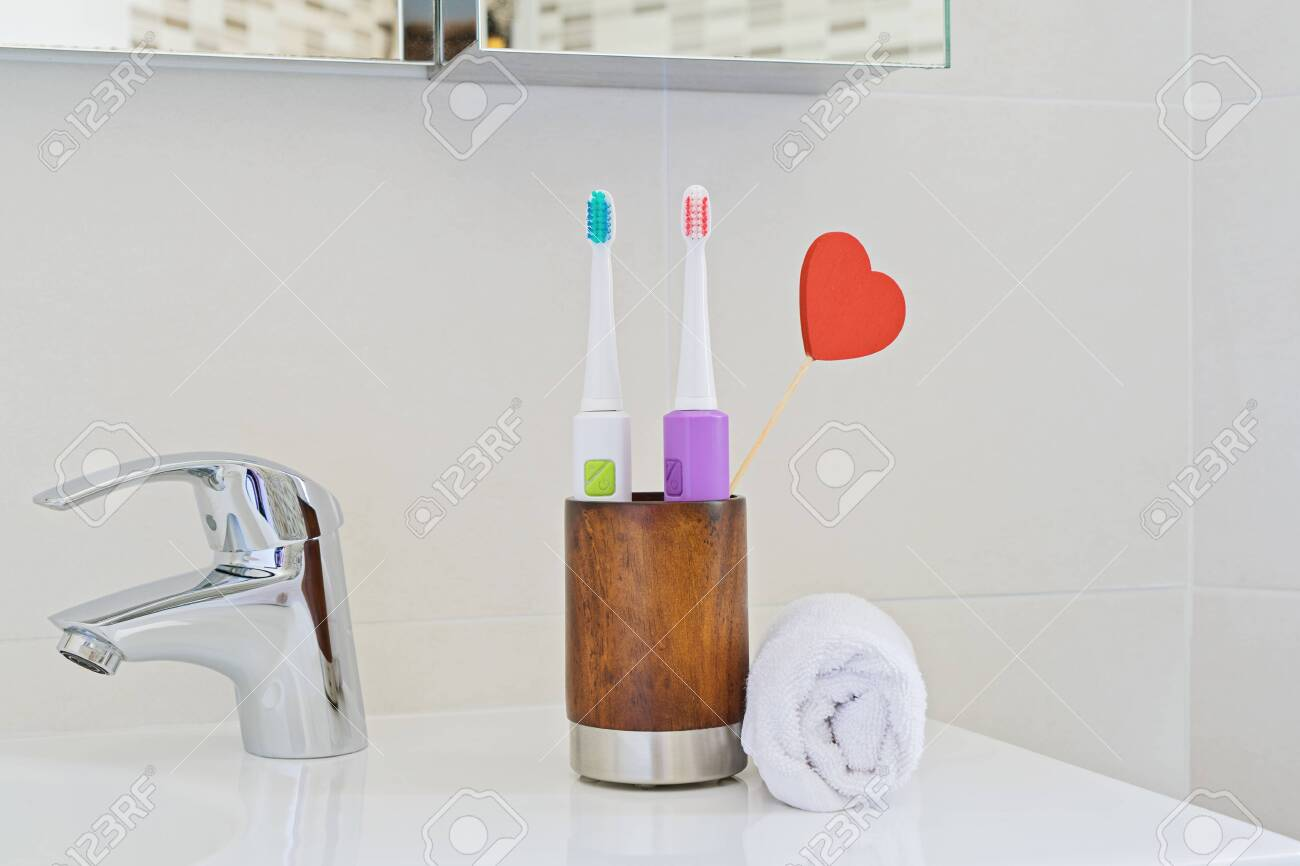 Awesome Two Electric Toothbrushes In Wooden Glass On Sink In Bathroom Interior Design Ideas Gentotthenellocom