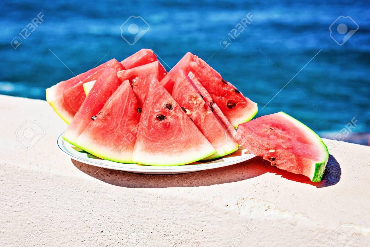 Pieces Of Ripe Watermelon Cut Into Triangles On The Blue Sea