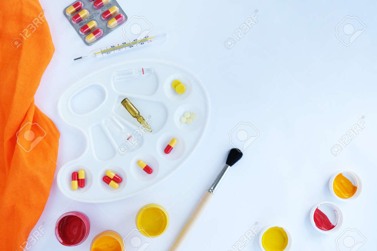 On a white background, a palette for paints and in it are pills, ampoules and a thermometer, next to it there are paints with a brush. - 157773645