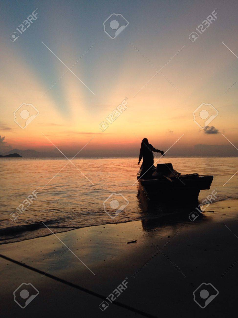 a woman standing on a boat eagerly waiting for the sunrise stock