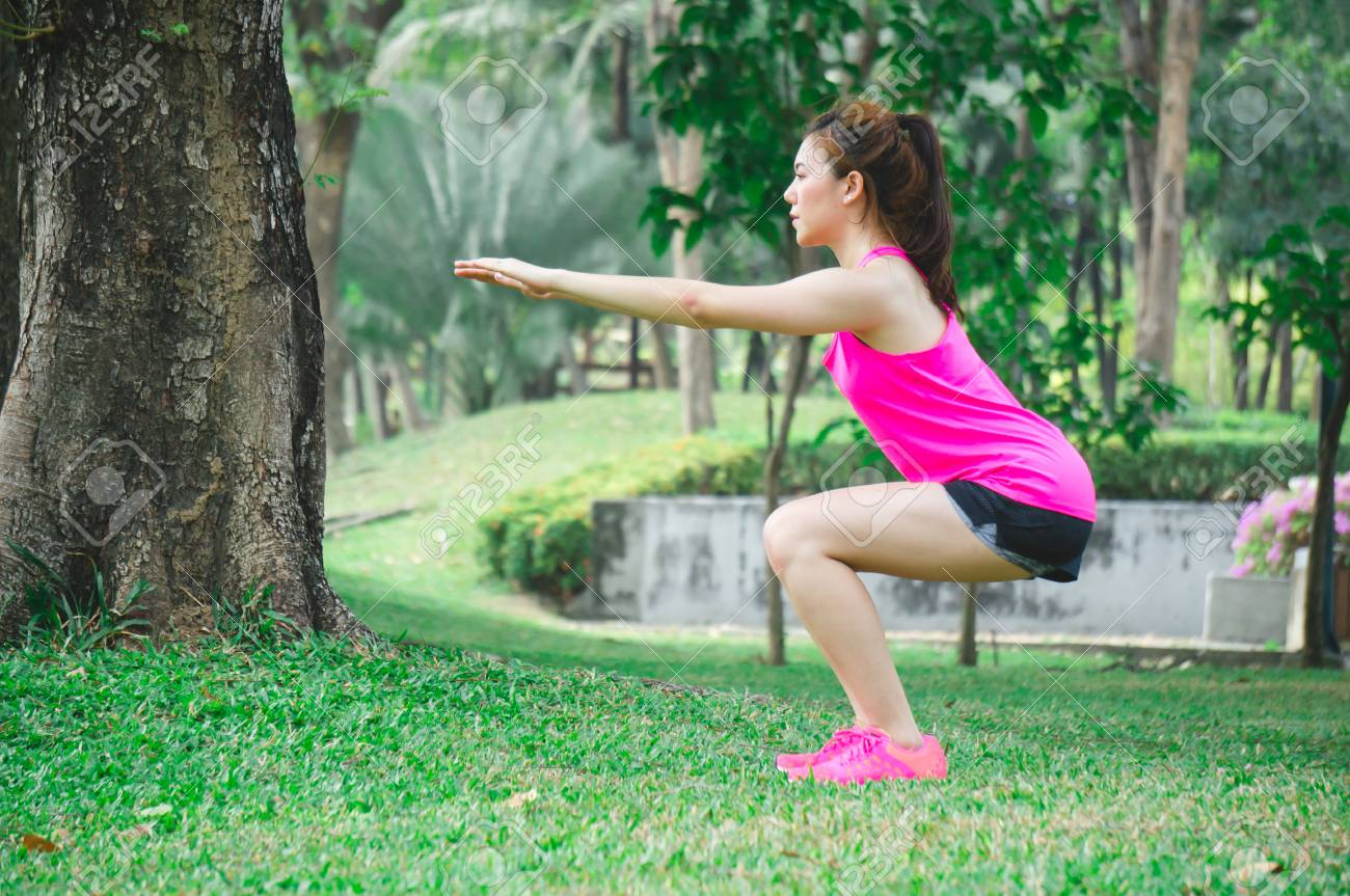 a070d0cd2bdbb Asian sport woman warm up to exercise by body weight squat in park for  health Stock