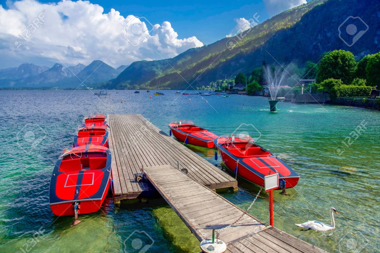 Red boats in summer time with swan in lake in Austria, Europe - 115023932