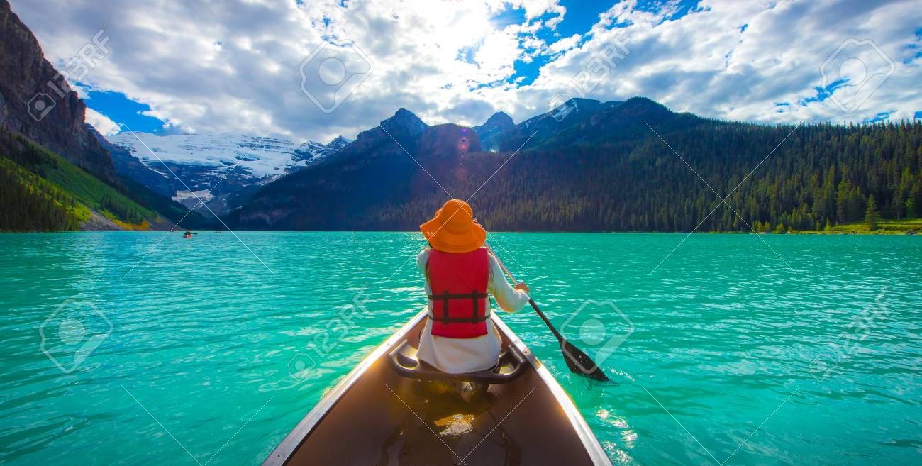 A woman in red life jacket canoeing in Lake Louise with torquoise lake and bluesky , Lake Louise, Alberta, Canada - 115023900