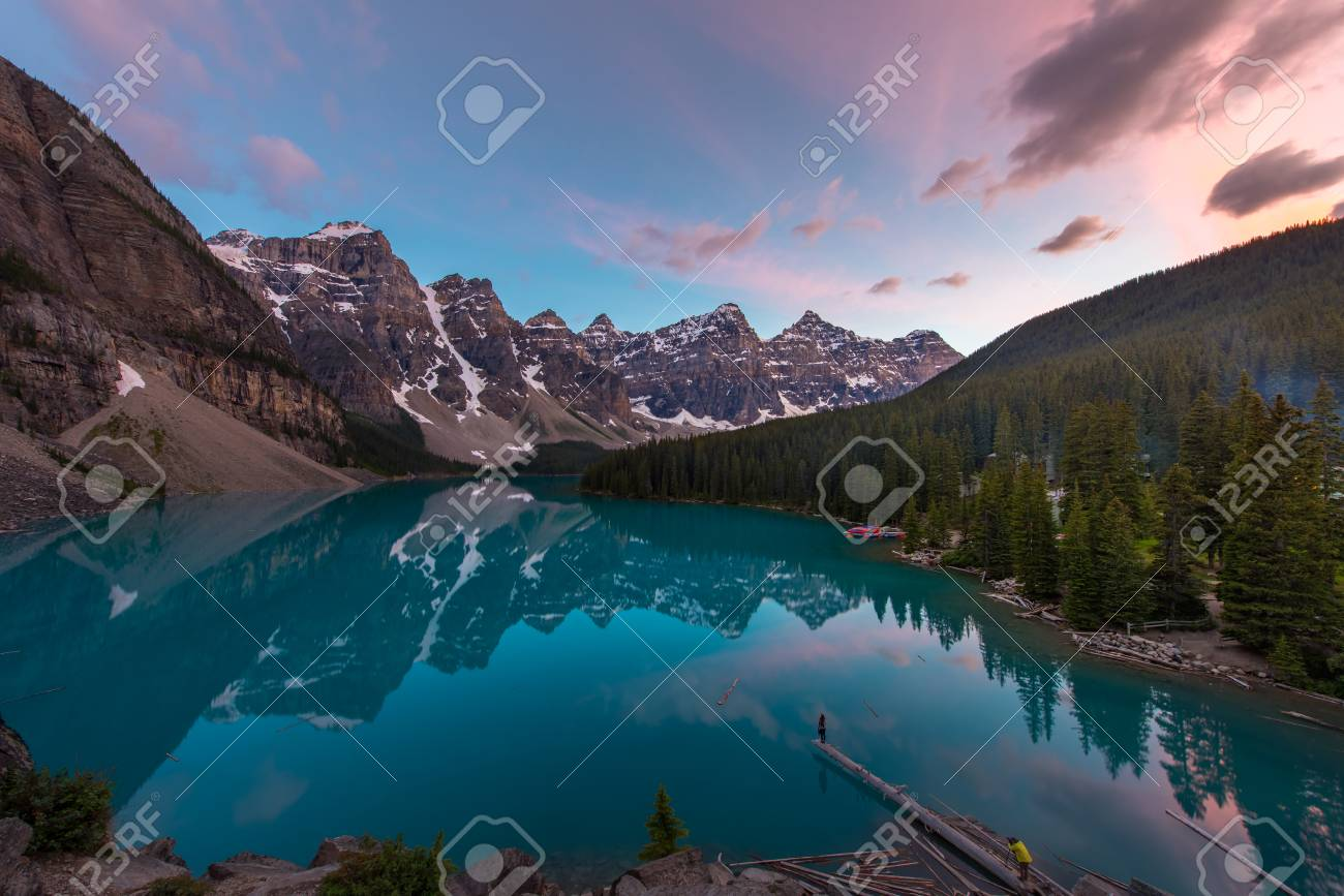 The Moraine Lake with turquoise lake and mountain reflection in sunset beautiful sky and photographer taking model by the lake - 115023907