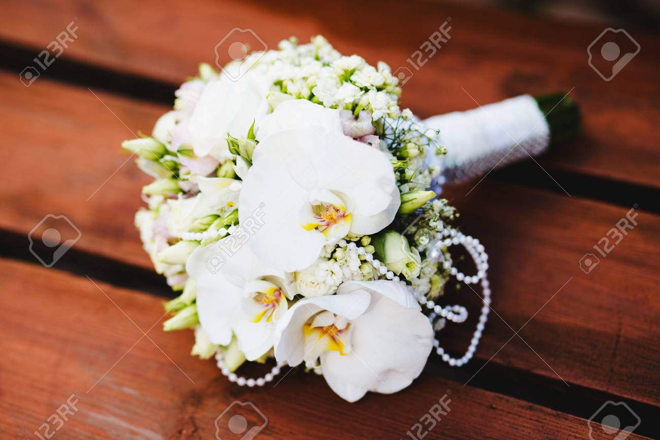 White wedding bouquet of flowers on a green background flowers stock photo white wedding bouquet of flowers on a green background flowers lie on a wooden surface izmirmasajfo