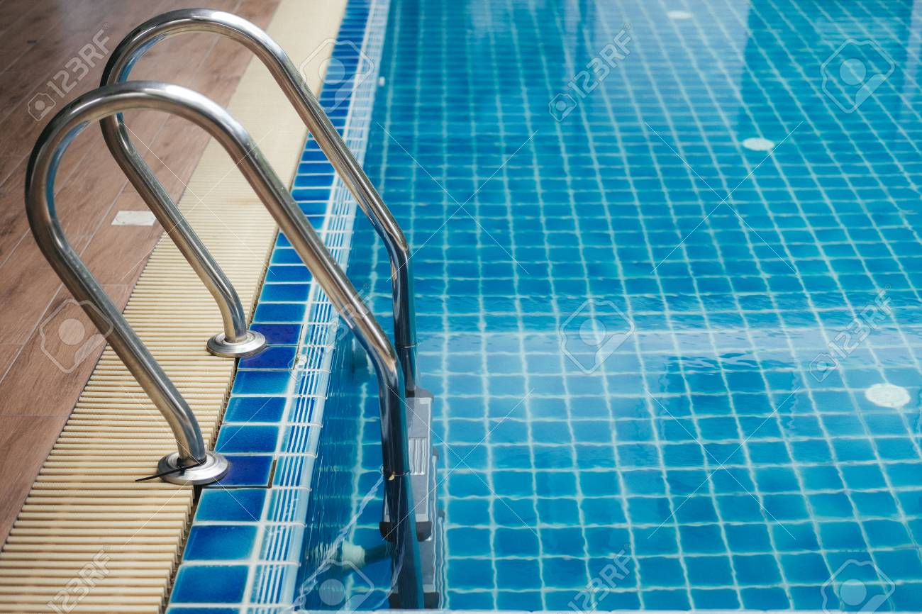 outdoor swimming pool with stainless steel stairs and clear water...