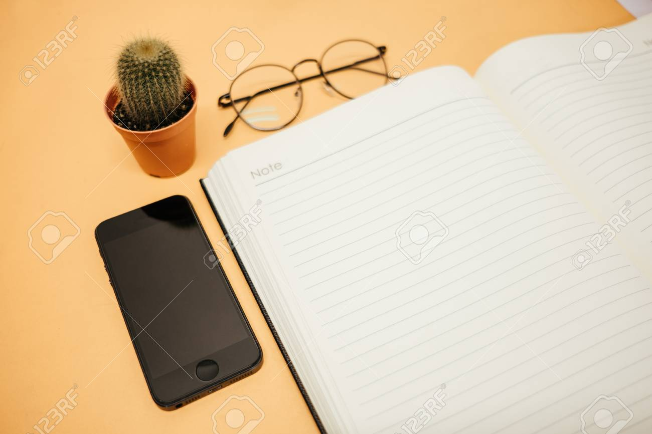 top view business background workspace with glasses, mobile phone,
