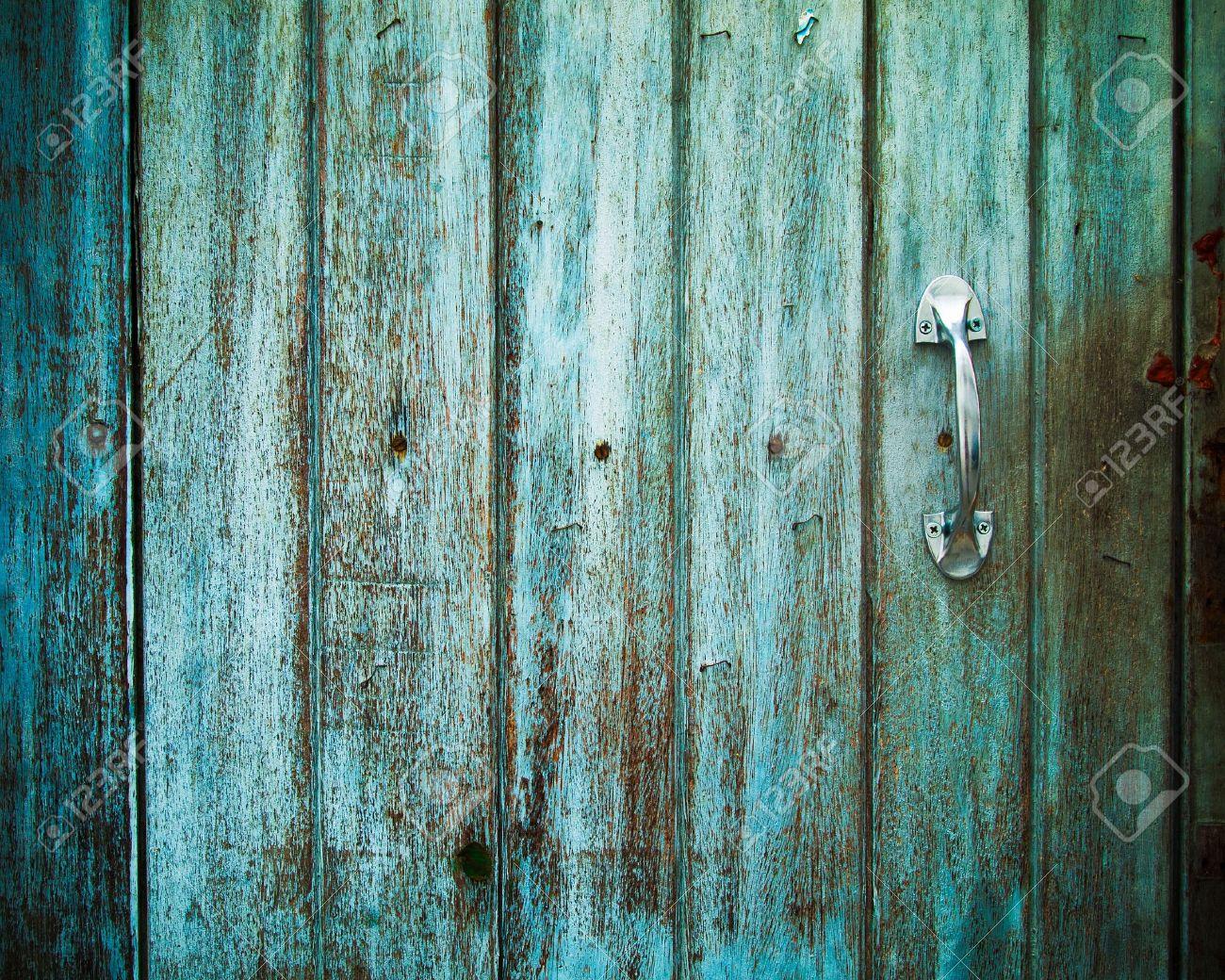 antiguo mango de puerta con una antigua puerta de madera pintada con el color verde