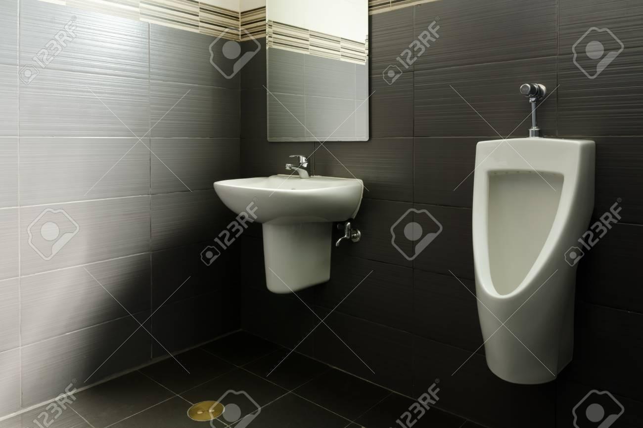 Witte Badkamer Wastafel : Witte keramische wastafel en urinoir in het donker badkamer