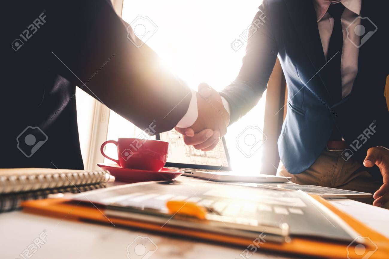 Two confident business man shaking hands during a meeting in the office, success, dealing, greeting and partner in sun light - 110433520
