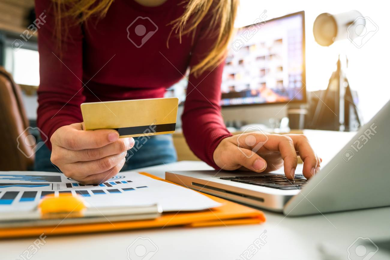 Business woman hands using smartphone and holding credit card