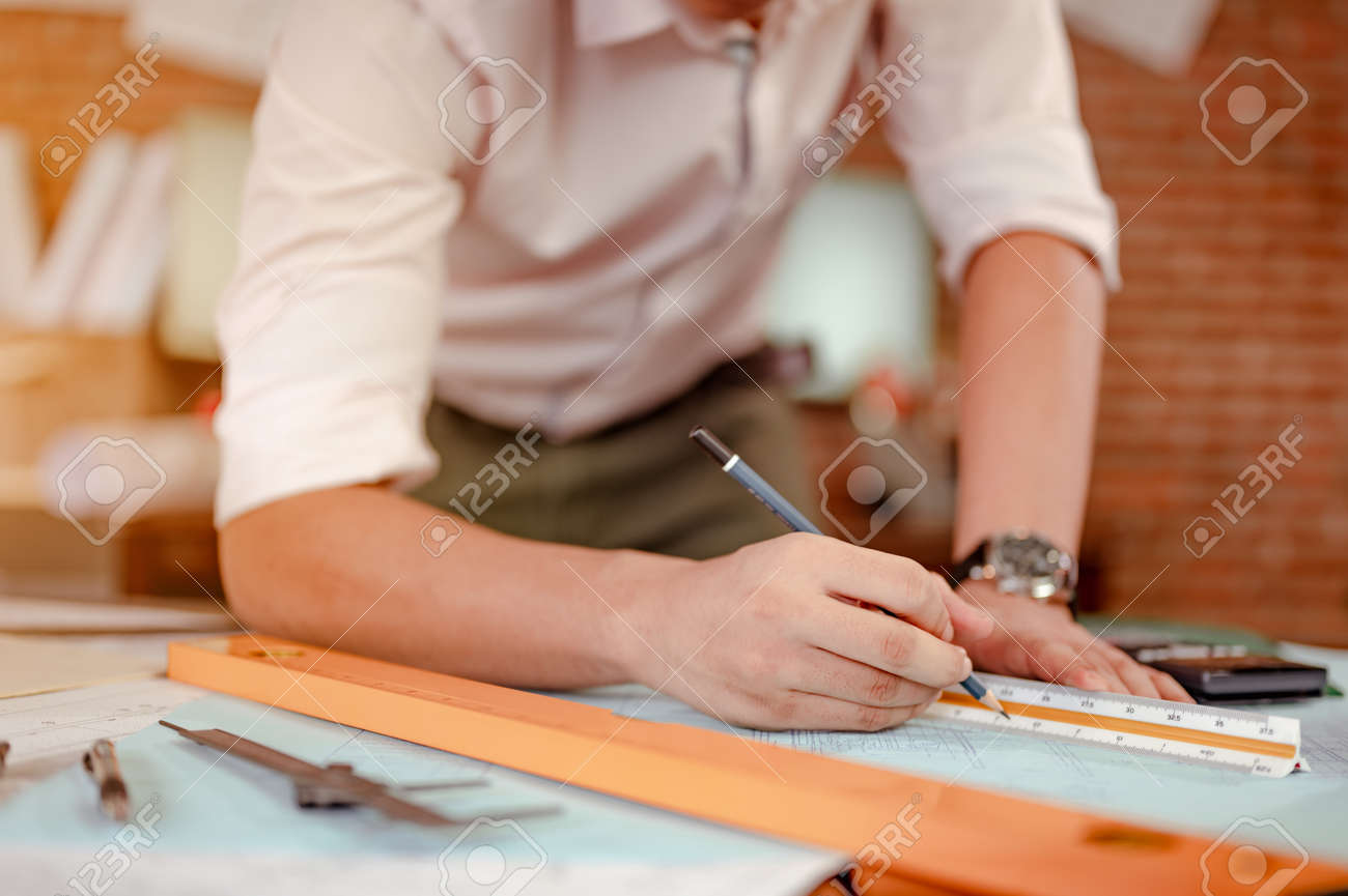 Close up of male architect hands measuring and making model house on the desk at sunset. Engineer, Engineering, Architecture, Design, Planning, Occupation concept. - 145876132