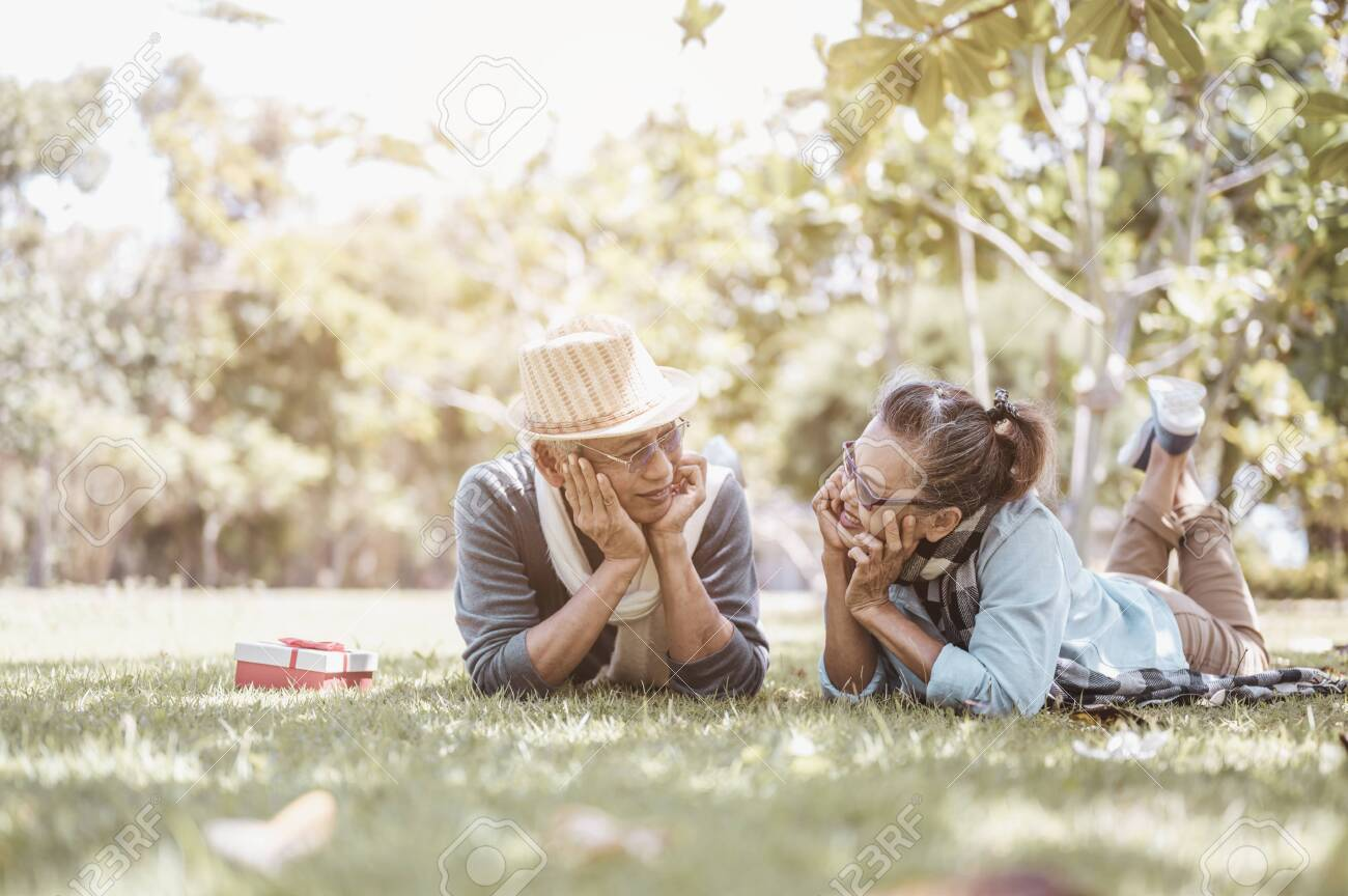 Senior, couples, retirement, insurance, elderly, lifestyle concept. Senior couples sitting and talking on the outdoor lawn in the morning about life insurance plans with a happy retirement concept. - 146211005