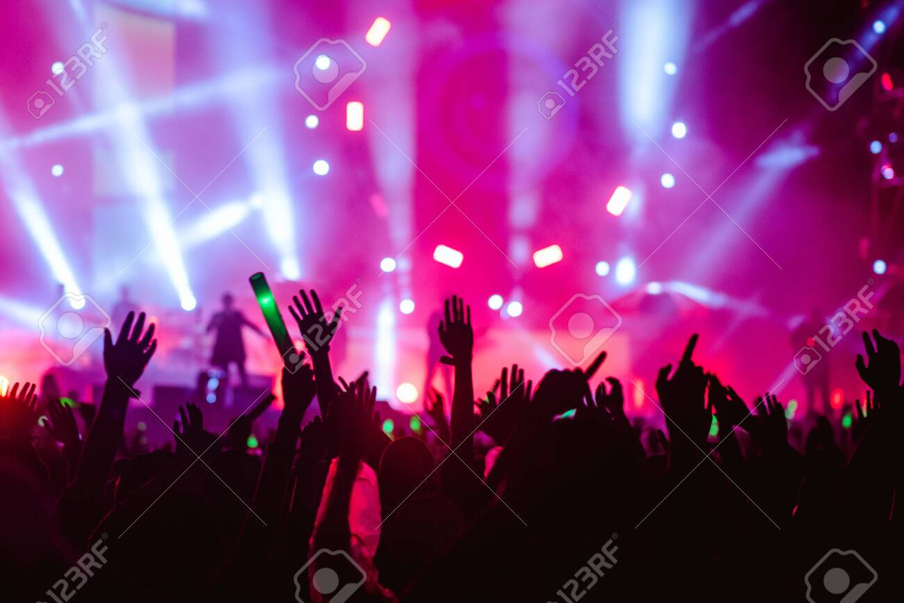 silhouettes of hand in concert.Light from the stage. - 145966914