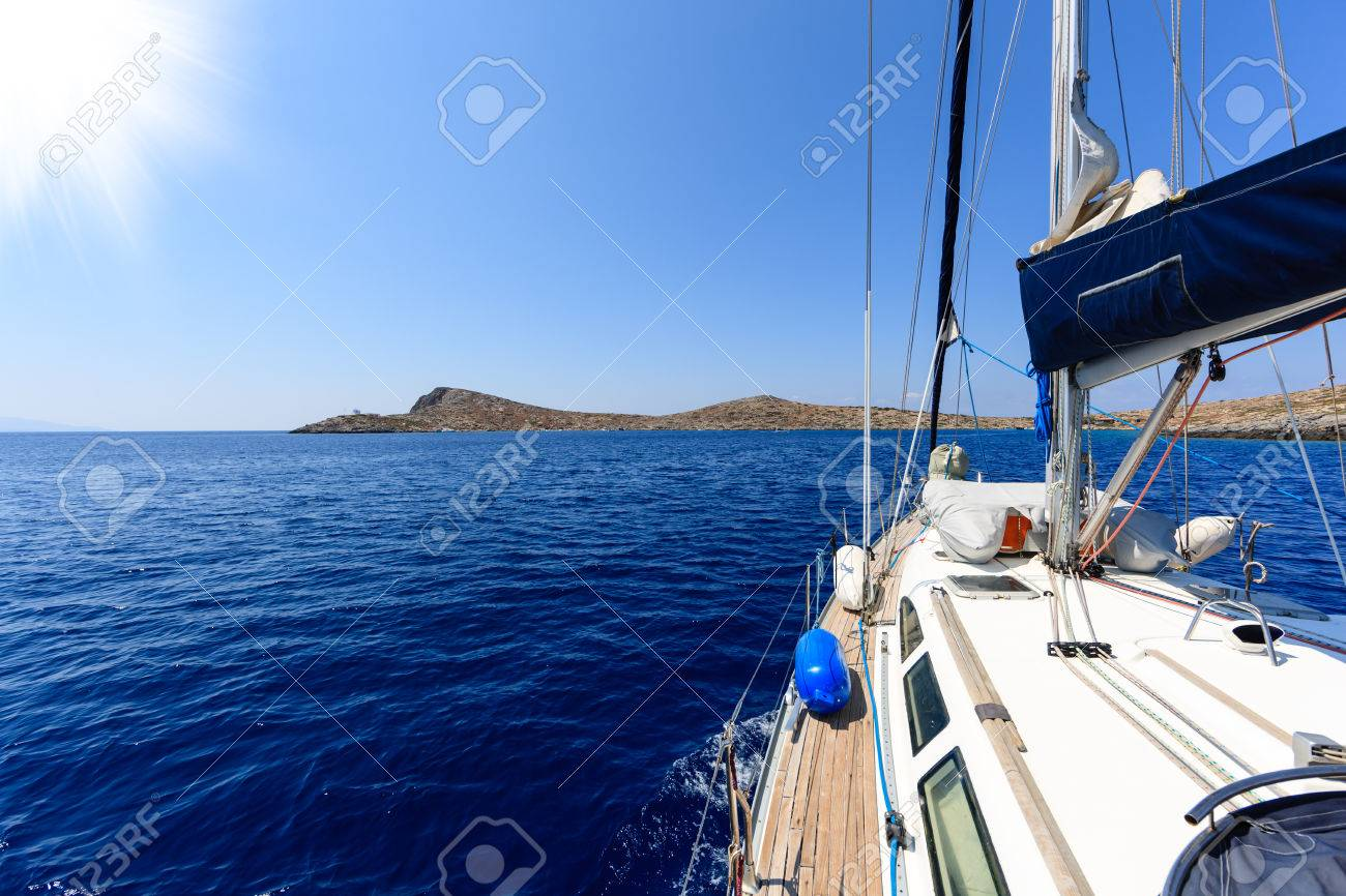 Tropical Island Yacht View Of A Tropical Island On The Horizon In A Calm Blue Sea From