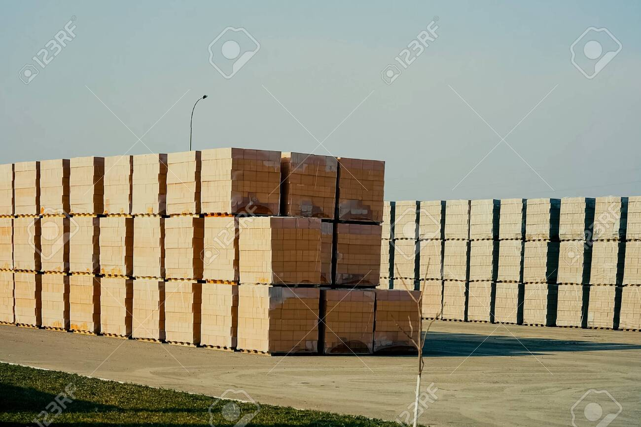Bricks are stored in an open-air warehouse. Red brick in pallets. - 140765427