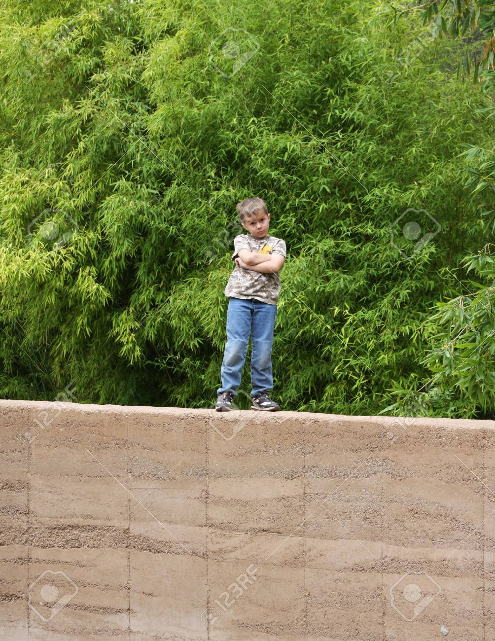 Young boy with defensive expression standing on wall Stock Photo - 3209131