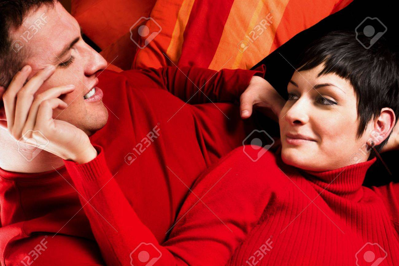 Young couple is enjoying the comfort of their home. They are looking at each other in an intimate moment. Stock Photo - 428202