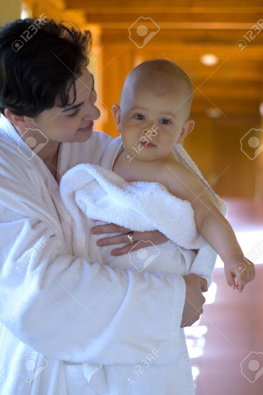 Mother and her 11 months old baby are ready to take a bath. They are weraing white bathrobe and towels. Stock Photo - 474894