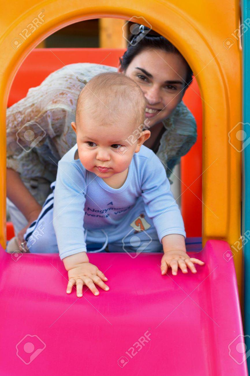 Baby and his mother are playing togather on a playground. Stock Photo - 474888