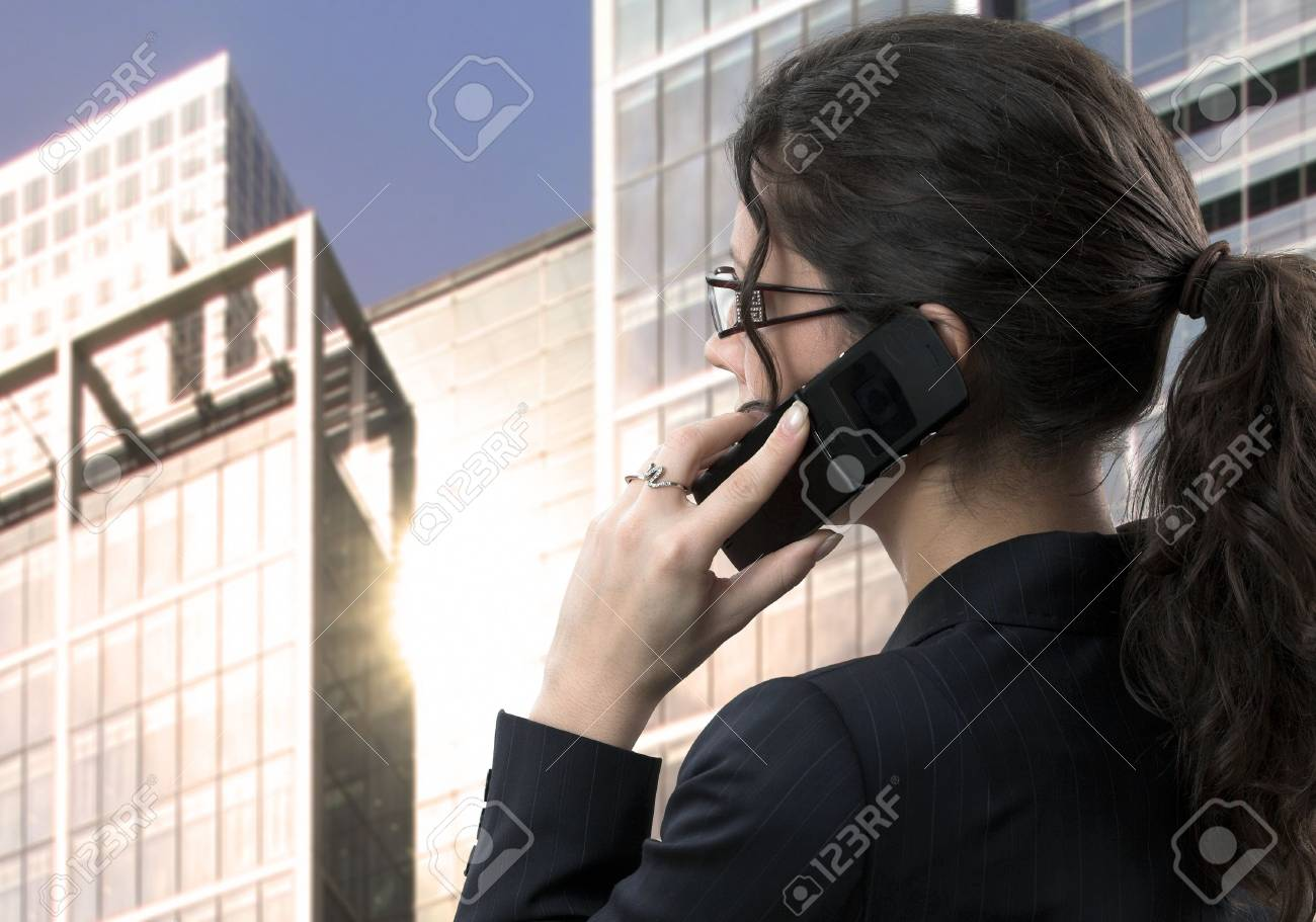 Young businesswoman talks on a mobile phone in the business area of the town. Stock Photo - 830554