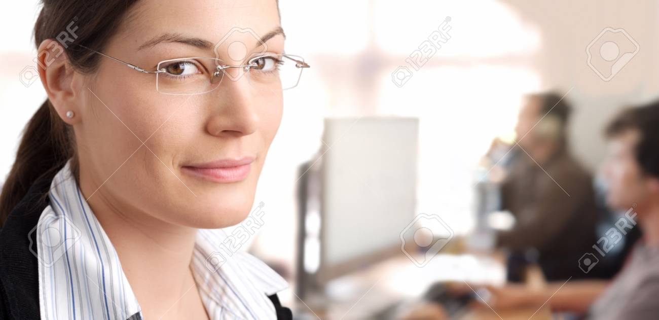 Young female manager stands in the office with IT specialists are working in the background. Stock Photo - 1422582