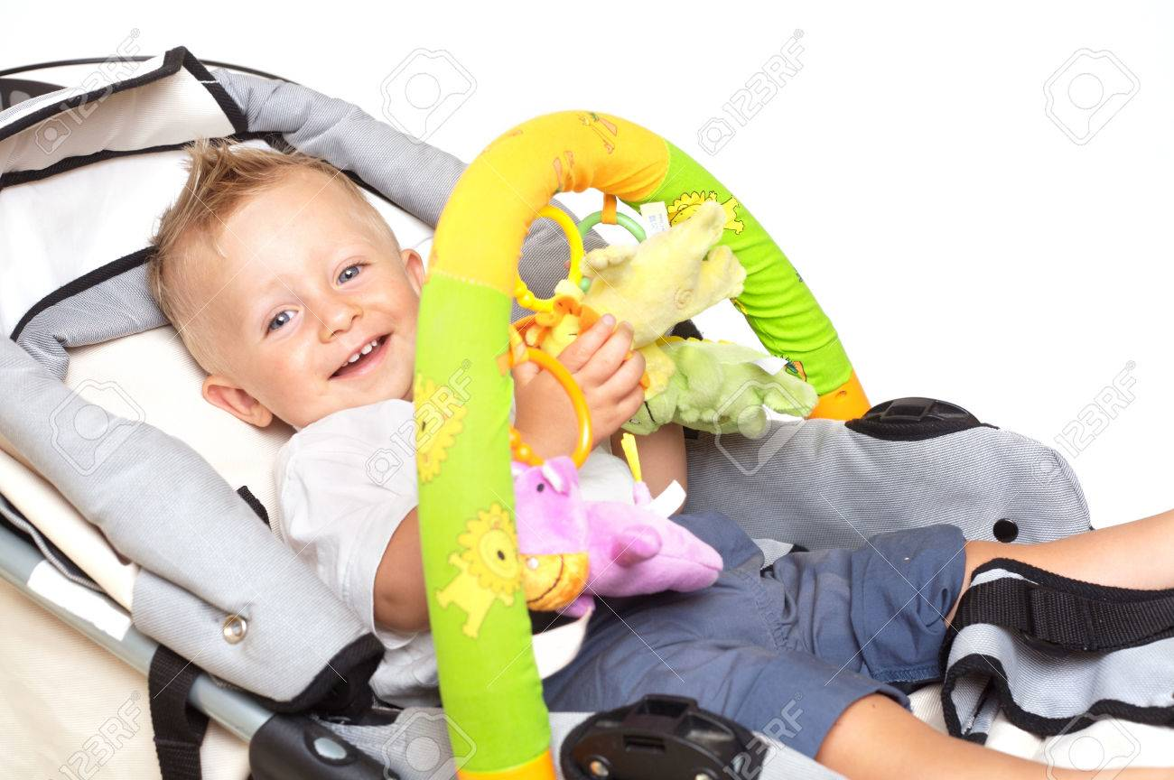 One year old baby boy is sitting in a stroller, smiling and playing with toys. All toys visible on the photo are officialy property released. Stock Photo - 1413585