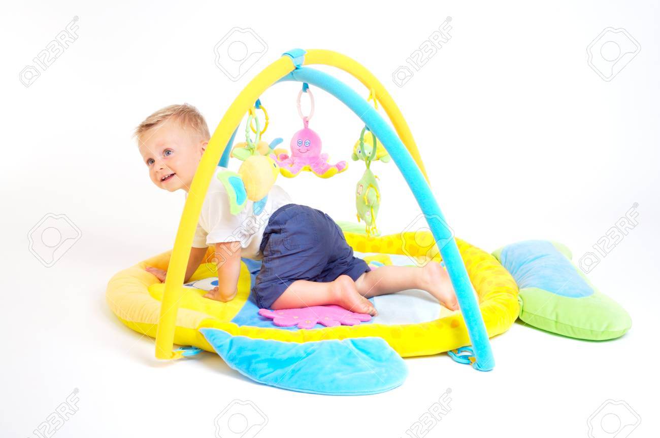 One year old  boy enjoys playing with toys. Studio Shot. All toys visible on the photo are officialy property released. Stock Photo - 1414167