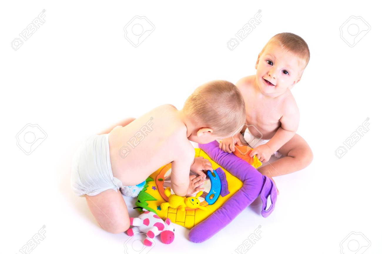 Twin baby boys are plaing together. Studio shot. All toys visible on the photo are officialy property released. Stock Photo - 1414403