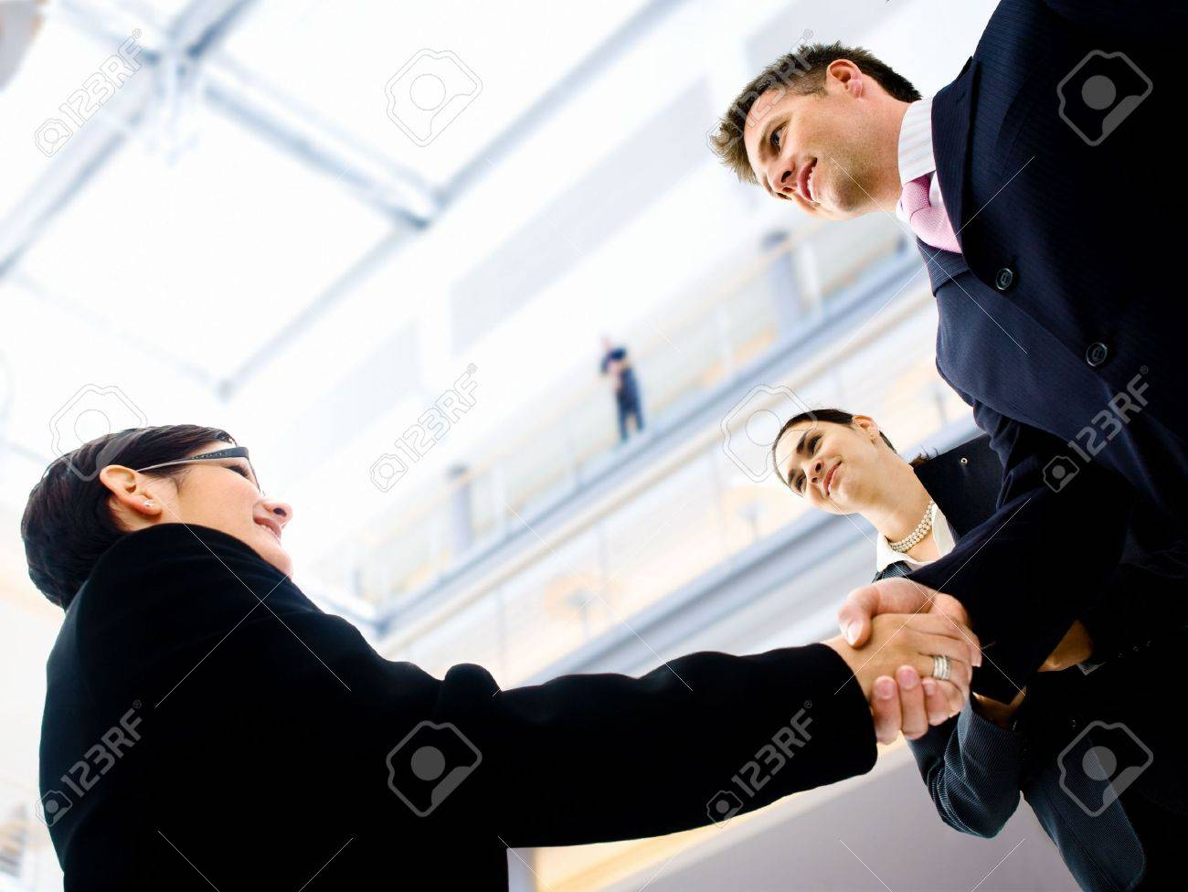 Business people shaking hands in the entrance hall of the office building. Selective focus is placed on the hands. Stock Photo - 1809592