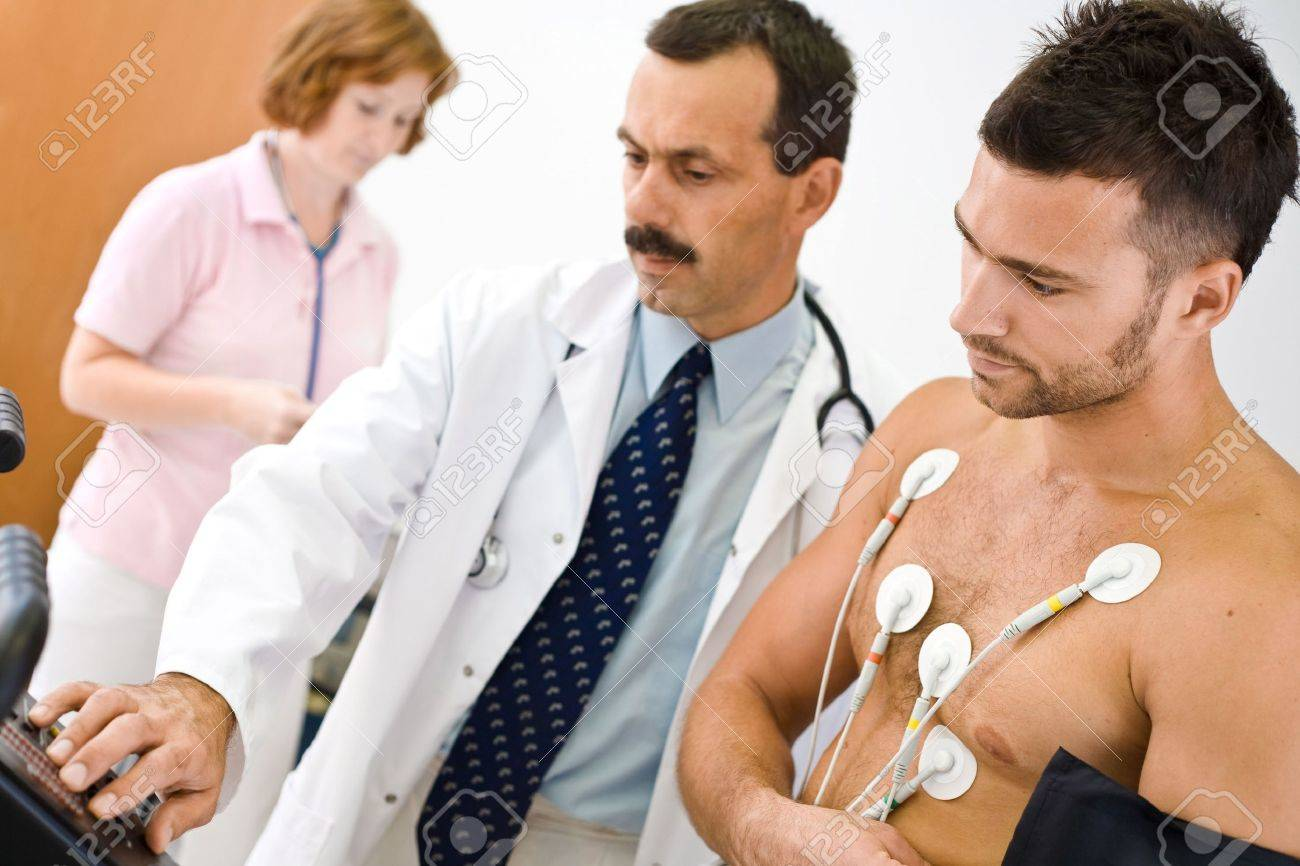 Medical team performing an EKG test on young male patient. Real people, real locacion, not a staged photo with models. Focus is placed on the patient. Stock Photo - 1989253